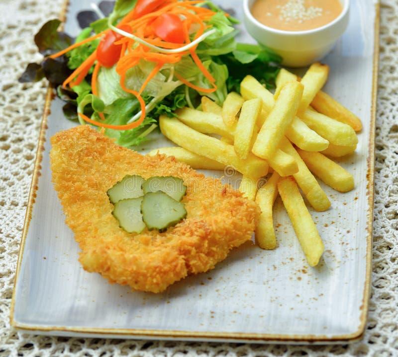 Pescados fritos con la ensalada de las verduras en fondo de madera imagen de archivo libre de regalías