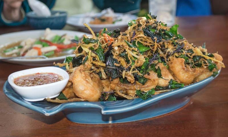 Pescados fritos con las hierbas tailandesas imagen de archivo