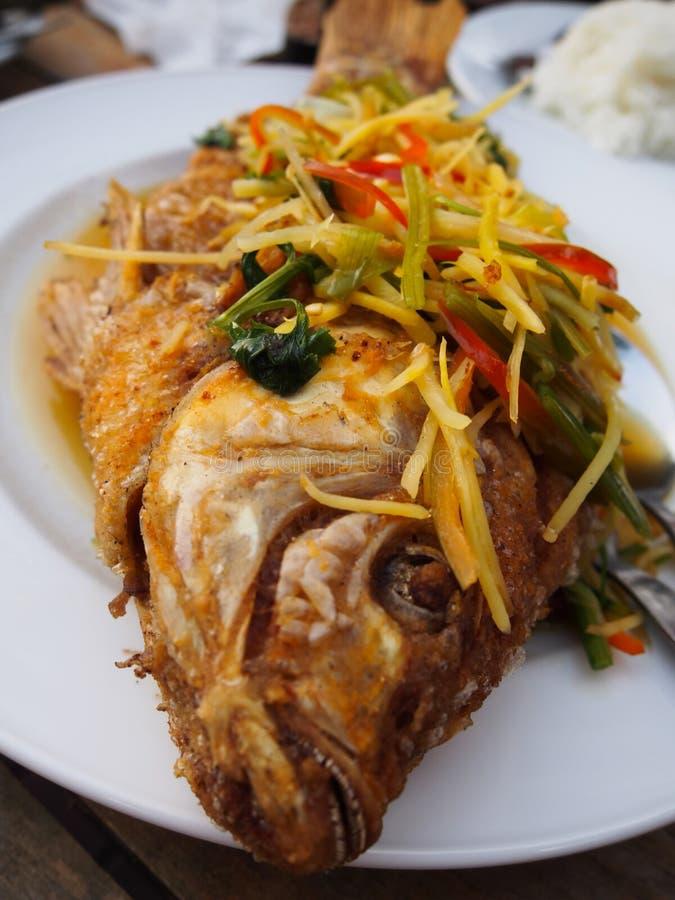 Pescados fritos en agitación de gran tamaño con el jengibre, el coriandro y el chile Aderezo con una salsa en una placa blanca imagen de archivo