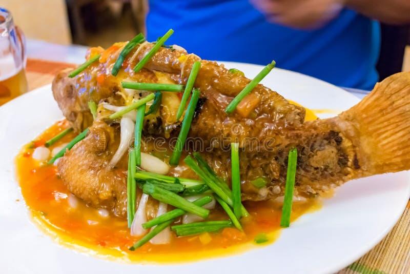 Pescados fritos en salsa con la cebolla verde en una placa en un restaurante foto de archivo