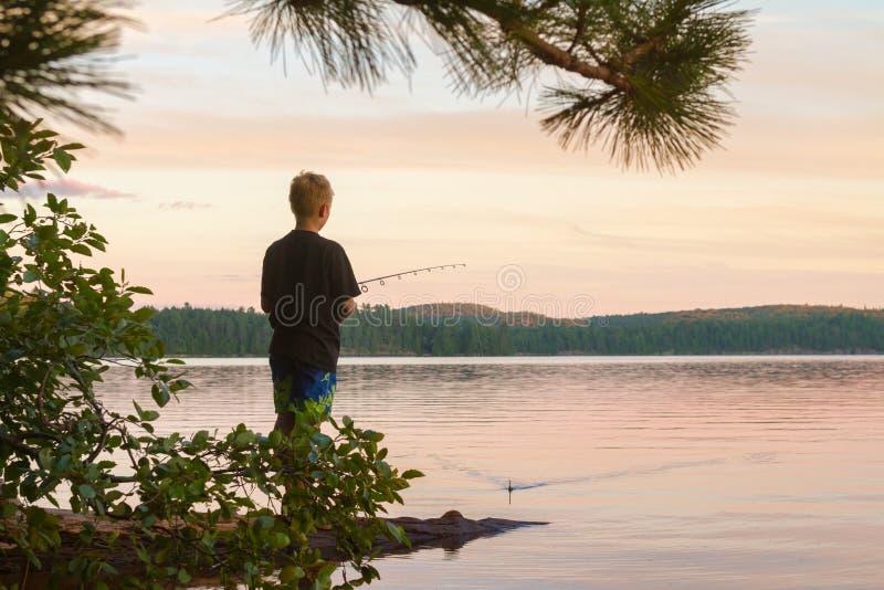 Pescados jovenes del muchacho en un lago en la puesta del sol fotografía de archivo libre de regalías