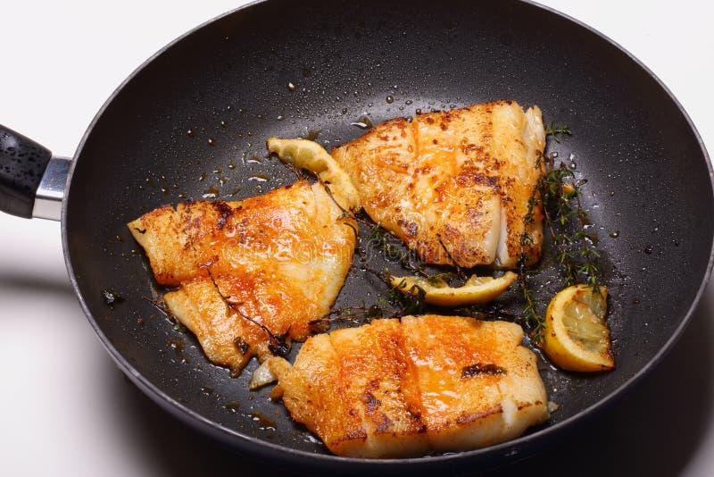 Pescados que cocinan en sartén foto de archivo