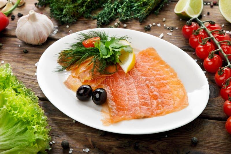 Pescados - salmones salados cortados en una placa fotos de archivo