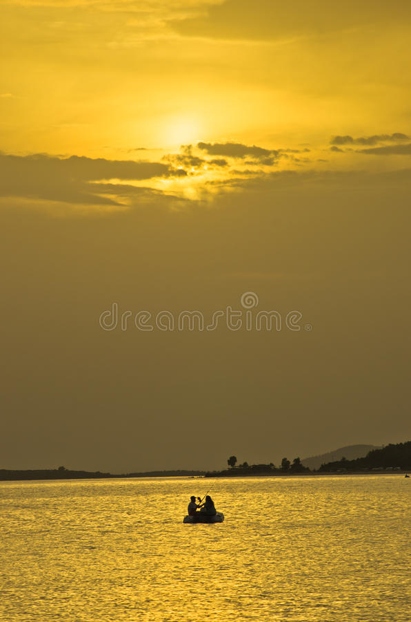 Pescando al tramonto nell'ambito dei fasci e delle riflessioni di luce gialla, Sithonia fotografie stock