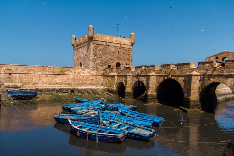 Pescando barcos, a engrenagem e a captura azuis bonitos no fundo de Castelo real de Mogador no porto velho de Essaouira imagem de stock