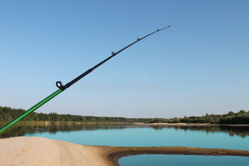 pescando, barretta di filatura contro il cielo ed il fiume fotografie stock libere da diritti