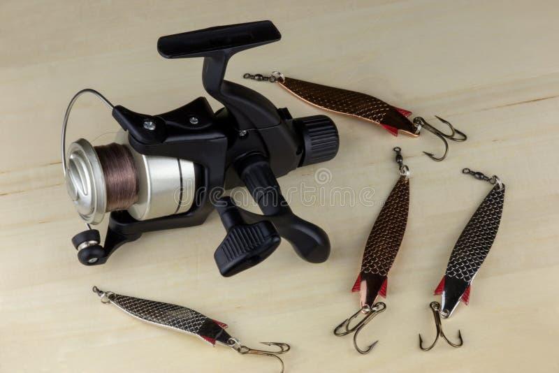 Pescando bobina e pesca dei richiami su una superficie di legno fotografia stock libera da diritti