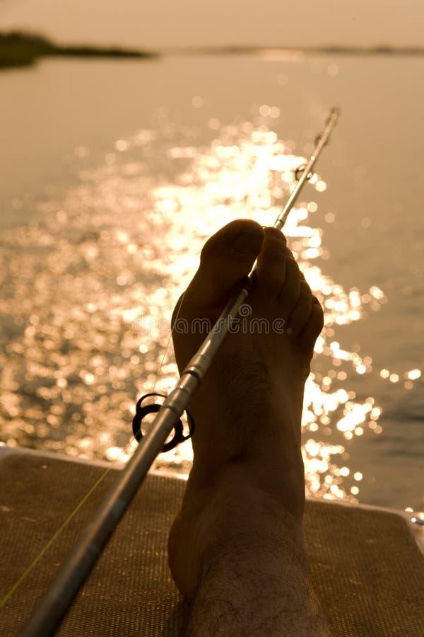 Pescando con il piede al tramonto fotografia stock