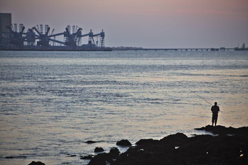 Pescando da solo alla bocca del Tago a Lisbona fotografie stock