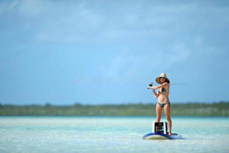 Pescando e paddleboarding nella destinazione tropicale fotografie stock