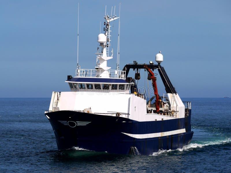 Pescando el barco rastreador en curso en aguas tranquilas foto de archivo
