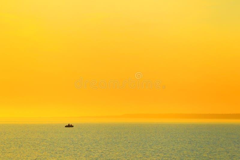 Pescando nel mare al tramonto immagine stock