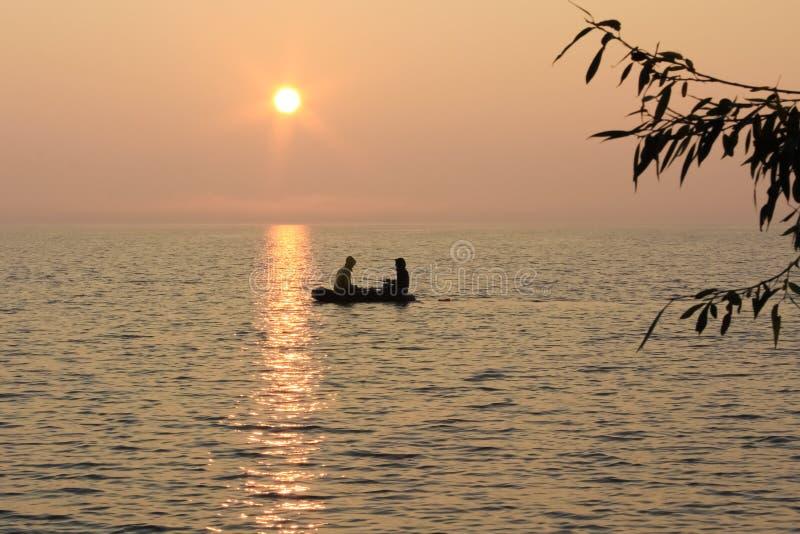 Pescando nella barca sul lago uguagliante fotografia stock