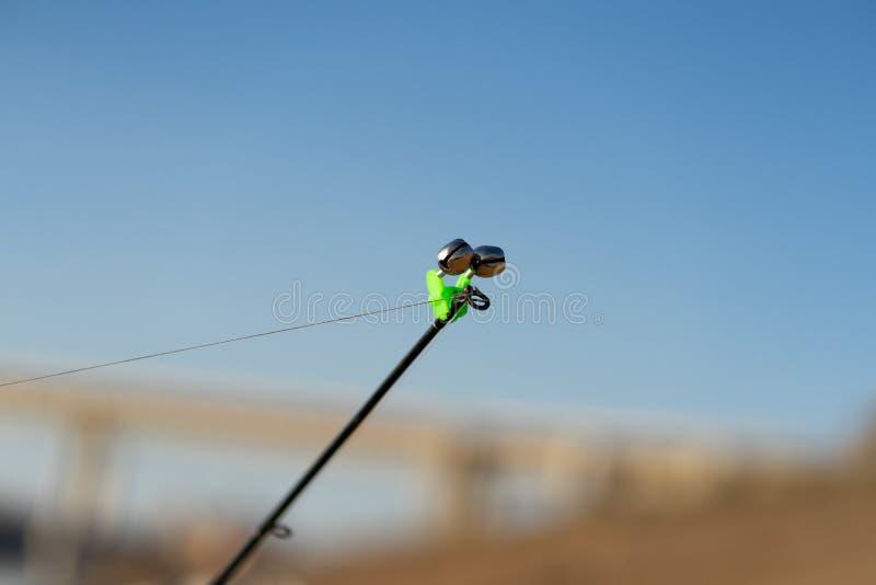 Pescando o sino na extremidade de uma vara de pesca Bels soar?o quando o peixe ? enganchado A ponta da vara de pesca com imagens de stock