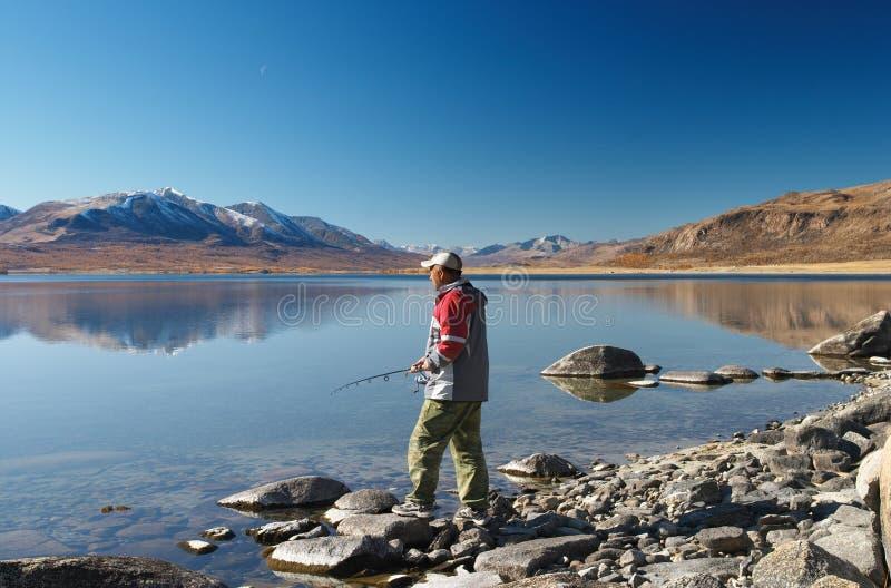 Pescando sul lago della montagna fotografia stock libera da diritti