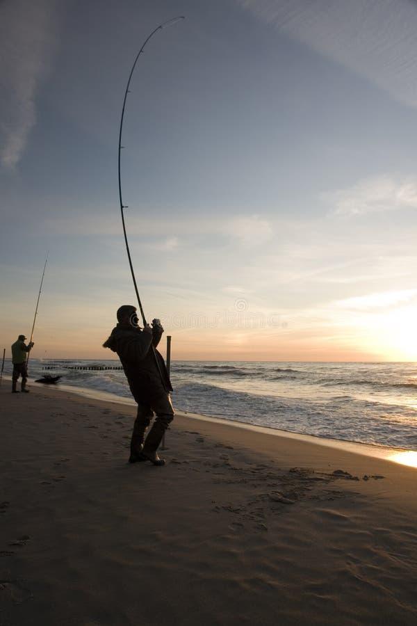 Pescando sulla spiaggia fotografia stock