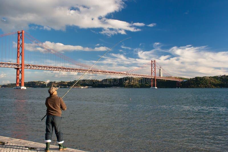 Pescatore al lungofiume di Lisbona I 25 il de Abril Bridge misurano il Tago del fiume e raggiungono oltre la statua di Cristo Rei immagini stock libere da diritti