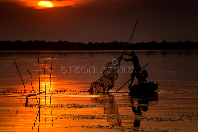 Pescatore al tramonto fotografia stock libera da diritti