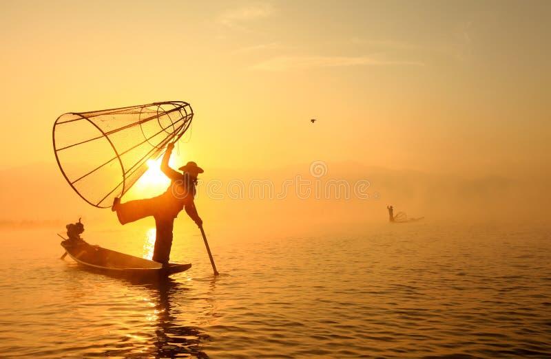 Pescatore birmano sul pesce di cattura della barca di bambù fotografie stock libere da diritti