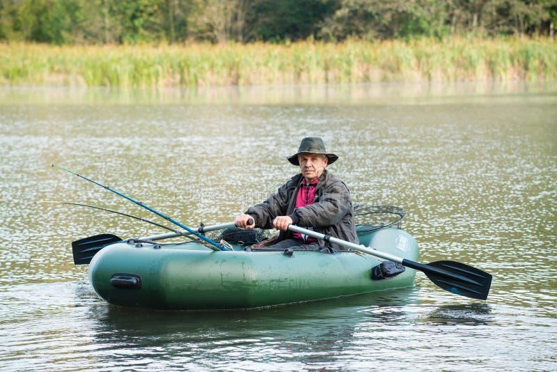 Pescatore caucasico che prova a pescare pesce sul lago al giorno soleggiato fotografia stock libera da diritti
