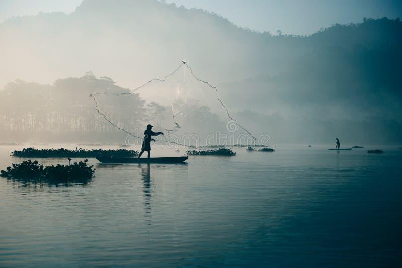 Pescatore che fonde fuori la sua rete da pesca nel fiume presto nel blu colorato mattina per pescare pesce fotografie stock