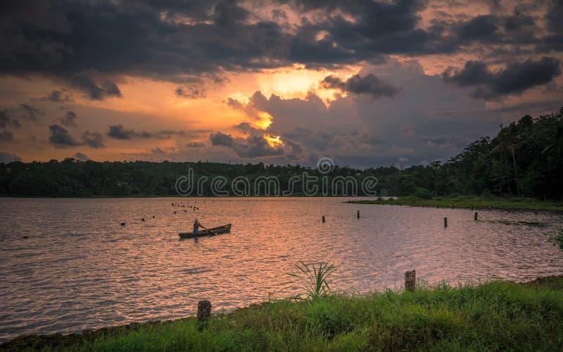 Pescatore che rema canoa nel tramonto nel lago Cheloor immagine stock
