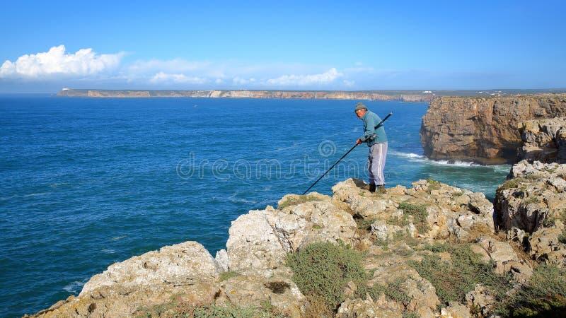 Pescatore che si inclina sopra le alte scogliere alla fortezza Fortaleza di Sagres con il faro di Cabo de Sao Vicente nei precede immagine stock