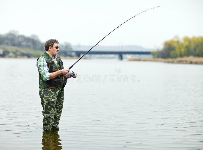 Pescatore che si inclina sul fiume fotografia stock