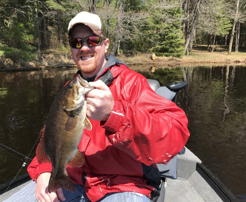 Pescatore che tiene una spigola di Smallmouth fotografie stock libere da diritti