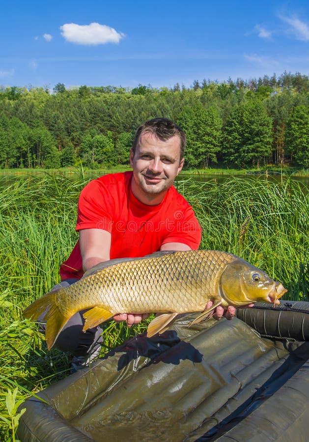 Pescatore con il trofeo del pesce della carpa immagini stock libere da diritti