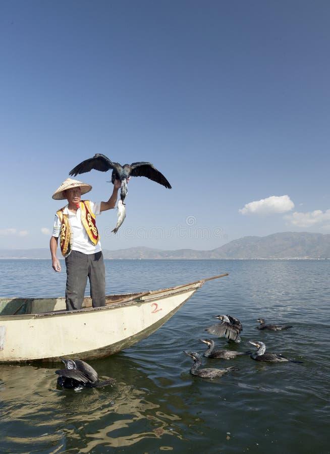 Pescatore con l'uccello ed i pesci fotografia stock