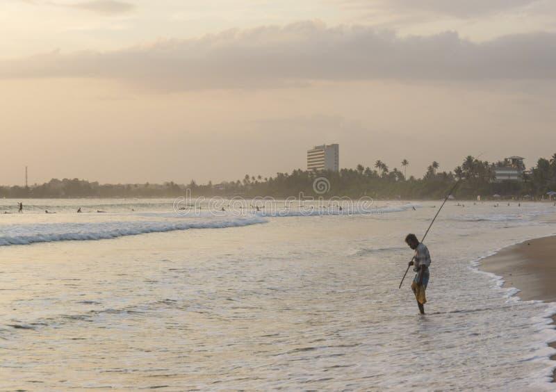 Pescatore con la canna da pesca che sta sulla spiaggia fotografia stock libera da diritti