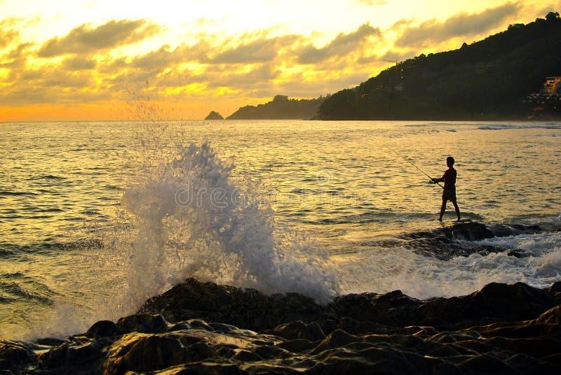 Pescatore con la grande onda della spruzzata