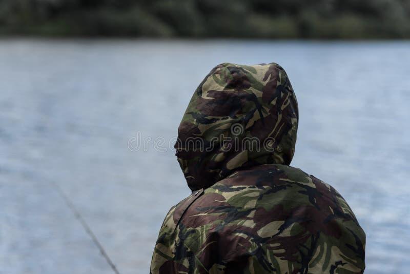 pescatore con un alimentatore davanti al fiume fotografie stock libere da diritti
