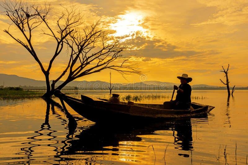 Pescatore della siluetta sulla barca del pesce sul lago nella mattina del sole fotografia stock libera da diritti