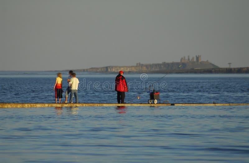 Pescatore e famiglia sul porto fotografia stock
