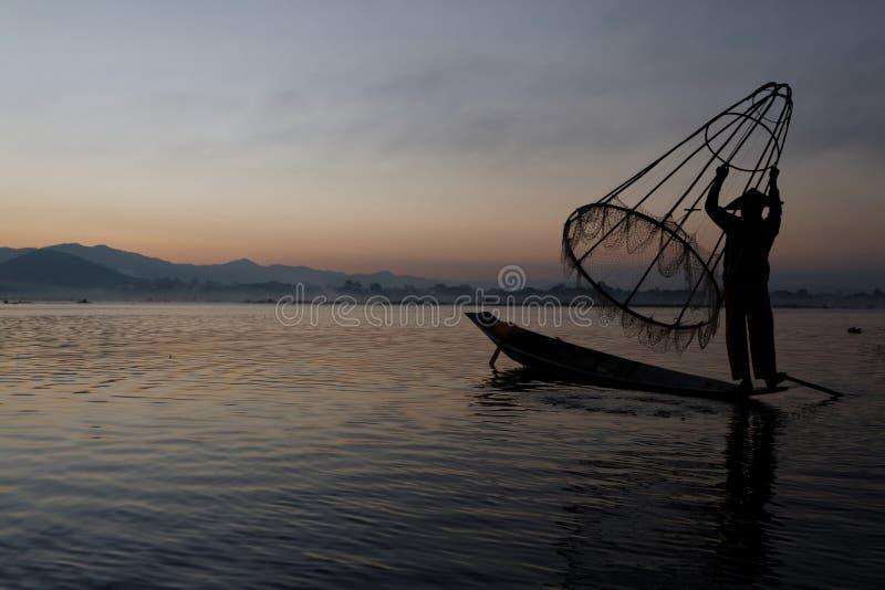 Pescatore ed il suo alto a rete fotografie stock