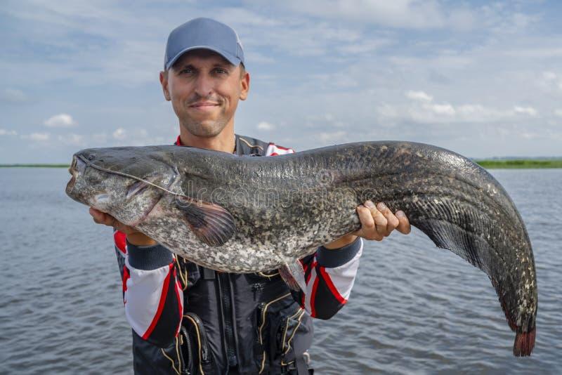 Pescatore felice con il grande trofeo del pesce del pesce gatto alla barca con le attrezzature di pesca immagine stock