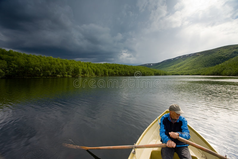 Pescatore maggiore in una barca fotografie stock