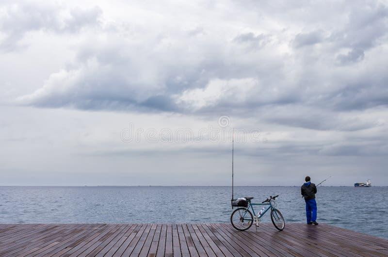 Pescatore nel lungomare di Salonicco, Grecia, sotto un cielo nuvoloso fotografia stock