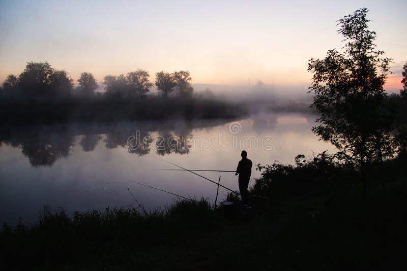 Pescatore solo che si inclina in un lago nel primo mattino appena prima alba fotografia stock