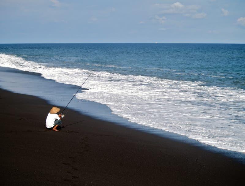 Pescatore su una spiaggia immagine stock