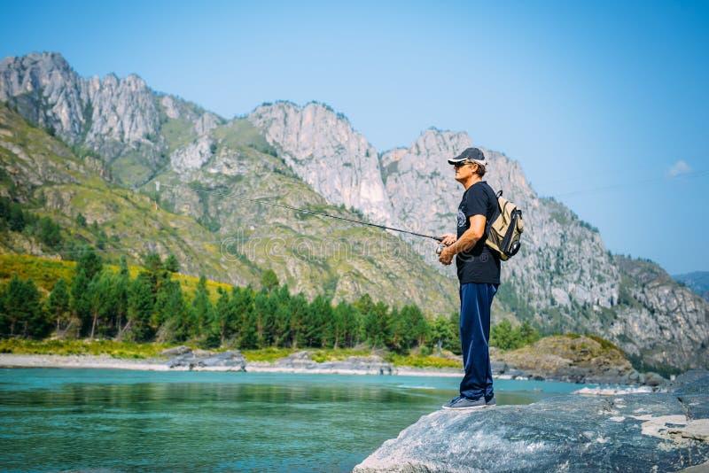 Pescatore sul fiume della montagna al giorno di estate piacevole Pesca con la mosca della trota nel fiume della montagna con le m fotografia stock