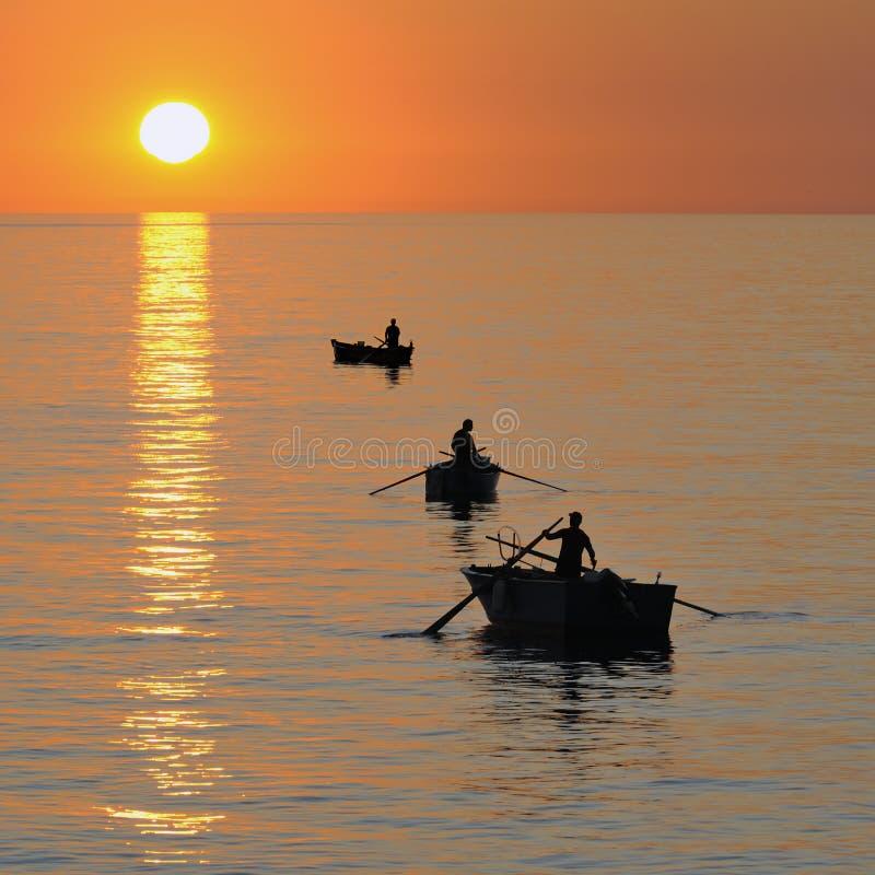 Pescatore sulla bella baia calma ad alba fotografie stock