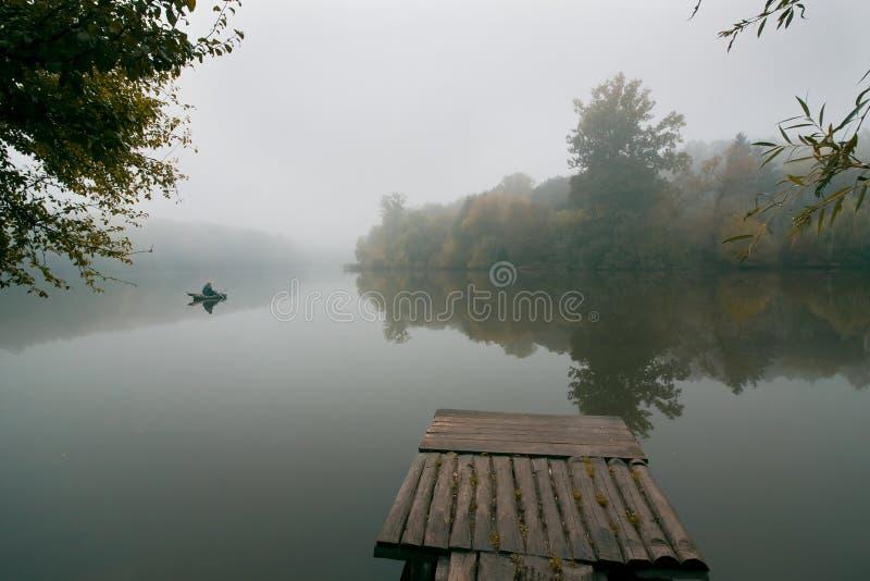 Pescatore in una pesca del gommone con i coni retinici su un piccolo lago, ancora superficie dell'acqua immagine stock