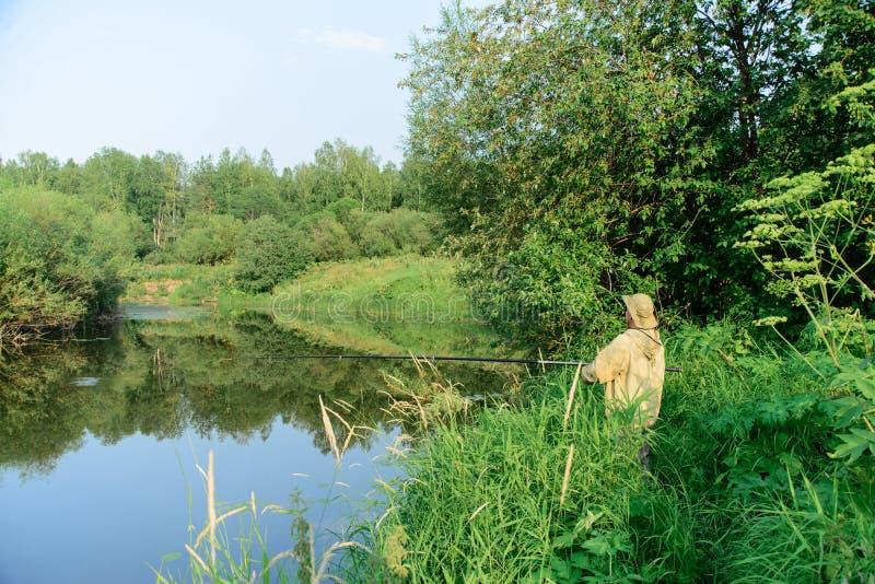 Pescatore in vestiti e nel pesce verdi del fermo del cappello sulla costa del fiume in erba fotografia stock libera da diritti