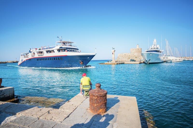 Pescatore vicino all'entrata nel porto di Mandraki in città di Rodi immagine stock libera da diritti