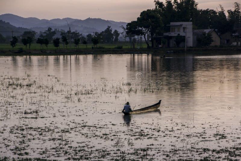 Pescatore vietnamita alla navigazione di tramonto su una barca lungo la riva immagine stock libera da diritti