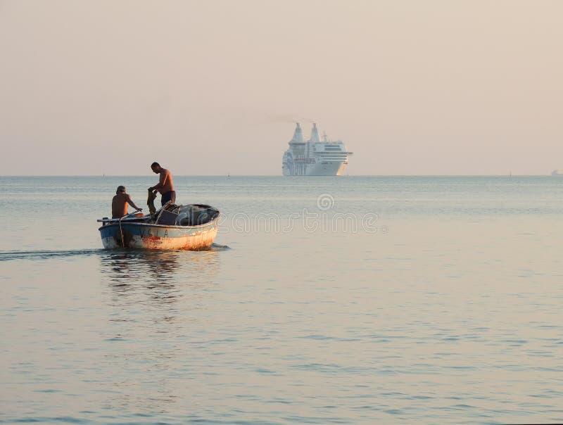 Pescatori albanesi in loro vecchio peschereccio, grande nave moderna nella distanza fotografia stock