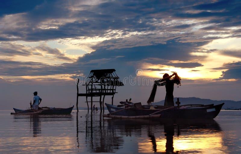 Pescatori asiatici con il tramonto. immagine stock